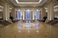 The entrance lobby at the Waldorf Astoria, New York has tile flooring, square columns, metal screens, decorative urns, high ceilings, and gold accents.