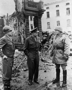 General Omar Bradley, General Dwight Eisenhower,  and General George Patton, all graduates of West Point,  survey war damage in Bastogne, Belgium in this 1945  photograph.