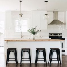 White kitchen, subway tile, butcher block island, stainless steel range hood