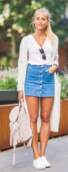 Jannie Deler is wearing this Summers most worn item, the button front denim skirts paired with a long cardigan and a fringe bag. Cardigan: Lindex, Top: Forever 21, Skirt: Gina Tricot, Bag: Maison Scotch, Shoes: Alberville. Denim Skirt Outfits