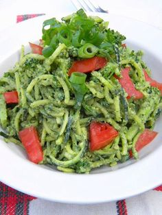 Ribbons of zucchini noodles sauced under a creamy, savory pesto with macadamia nuts, almonds, and fresh herbs combine with softened, gently spiced broccoli florets and fresh tomatoes.