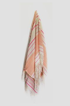 This large towel is made in Morocco from hand-loomed cotton and features orange and pink stripes with neutral fringing. Perfect for the beach or at home as a throw for your bed or couch. Dimensions: 175cm x 165cm