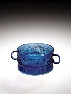 "Roman glass Ennion cup, 1-50 A.D. Transparent blue glassm body blown in four part mold, handles applied, on one side tabula ansata with inscription ""ENNIωN/ EПOIHCEN"" 'Ennion made [it]', in Greek flanked by vine sprays, on other side, tabula ansata with inscription ""MNHΘH/O AΓOPA/ ZNω"" 'May the buyer be remembered', in Greek, flanked by ivy ys, 6 cm high. Corning museum of glass For more Ennion glass please visit https://it.pinterest.com/andreacanecane/ancient-glass-ennion-glass/"