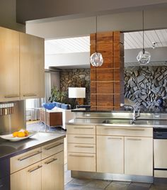 Mid-Century Marvel - Colorado Homes and Lifestyles - May 2014. Laminate cabinets and stainless steel countertops by Poggenpohl, installed twenty years ago, have timeless modern appeal. Comstock repeated the ipe wood design of the front door in columns throughout the house. Oversized pendants by John Pomp match the motif of the entry light fixture.