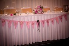 Pretty pink and white bunting and white drapery for wedding reception decor and top table