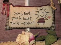 This primitive stitchery contains a sweet girl holding a flower created by hand embroidery with the hand stitched words of, You is Kind, You is