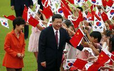 Park Geun-hye y Xi Jinping rodeados de banderitas en Seúl.