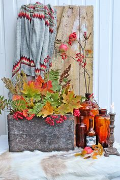 07 a stylish fall display with colorful bottles, candle holders, a concrete box with fall leaves and berries - Shelterness