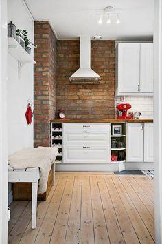 Deski z sękami i wiekowa cegła na ścianie nadają tej kuchni rustykalny klimat. Z wykończeniem ściany kontrastują białe profilowane meble ze stylowymi uchwytami. Na pograniczu aneksu kuchennego i przedpokoju stanęła ławka przykryta dla przytulności owczą skórą.