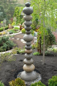 DIY garden art - Use a masonry bit and drill on each stone, and then place a piece of rebar into the ground to slide the stones onto