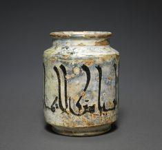 Albarello Jar with an Aphorism, 10th Century Central Asia, Samarkand, Samanid period earthenware with underglaze slip-painted decoration, Diameter - w:9.70 cm (w:3 13/16 inches) Overall - h:13.00 cm (h:5 1/16 inches). John L. Severance Fund 1996.298