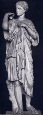 In this statue, Artemis is depicted in a short chiton, fastening a diplax at her shoulder with a fibula.