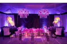 Glam Wedding Reception Rm with Ghost chairs, chandeliers & purple orchids