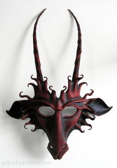 This goat mask is hand-shaped from high quality vegetable-tanned cow leather, from a template of my own design. It is painted inside and out in black, with highlights in a very deep burgundy red. The mask is lightweight and wearable, and comes with two removable leather laces attached. It is composed of five separate pieces of leather, all permanently and securely glued in place. The mask is ready to wear, or can be hung on the wall as a great display item. The size of the piece is…