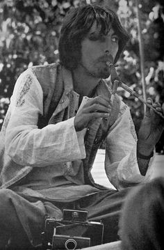 George Harrison (in India). This is cute, I wonder what instrument he's playing.