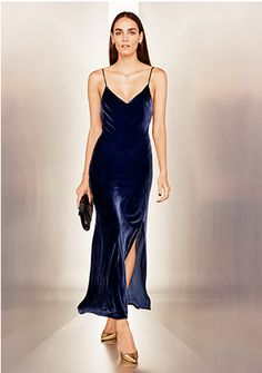 Exclusive for Intermix Addison Velvet Slip Dress: Take a plush velvet slip out of the bedroom for an elegant take on the dress. Adjustable grosgrain ribbon cross back straps. V neckline. Slit at leg. Lined. In navy or denim blue. Fabric: 82% rayon/18% silk Lining: 100% polyester Made in USA. Model ...