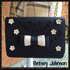 """HP Best in Bags Betsey Johnson Crossbody Flower laser cut w/raised double layer flowers w/gold tone in bloom all around front! Raised bow adorns this fantastic bag too! Fold over snap closure. Handle drop is 22.5"""" w/the last 5.5"""" in gold tone chain, beautifully drops thru top surrounded by gold tone. Backside has gold tone BETSEY JOHSON plaque. Inside is black lined w/silver sayings """"SWEETIE"""" """"ROCK IT"""" """"CALL ME"""" etc. Approx 6.5"""" zippered pocket w/BETSEY JOHNSON raised patch logo. Approx 3.5""""…"""