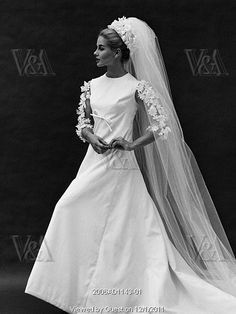 February Vogue 1960 A fragile generosity of white dotted Swiss organdie with a band and bow of narrow black ribbon. By Lilly Daché.
