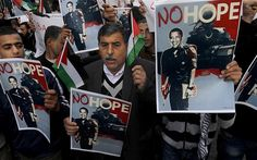 Palestinians hold posters depicting Barack Obama in an Israeli military uniform
