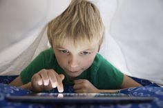 Boy using digital tablet in bed under blanket