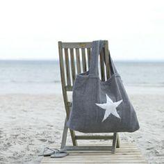 sac de plage gris, chaise au bord de la mer