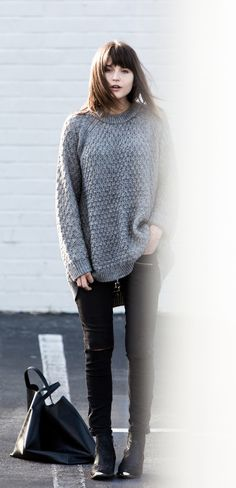 Rima Vaidila is wearing a grey knit oversized jumper from Pink Stitch