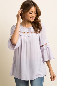 A solid hued blouse featuring a semi-sheer crochet accents, long wide sleeves, a rounded neckline, and a keyhole back with button closure. This style was created to be worn before, during, and after pregnancy.