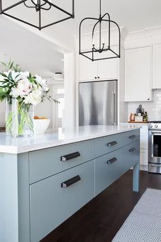 Beautifully blue and white kitchen features a stainless steel refrigerator recessed beneath off-white shaker cabinets painted in Benjamin Moore Silver Satin.