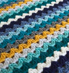 RIC RAC BLANKET A beginners crochet blanket in Ocean View colourway. Colours inspired by the sea in beautiful teals, blues with a splash of neutrals. The yarn is Deramores Studio DK (which is a beautiful yarn!). Shop the colour pack! Ocean View Colour yarn pack is available from Deramores. You can also purchase the pattern there. #crochet #crochetpattern #yarnpack #crochetblanket