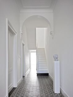 Tiled flooring creates character to a simple white hall way.