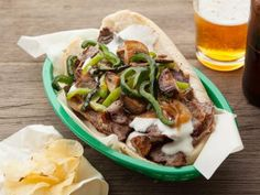 Philly Cheese Steak: It's hard to think of Philadelphia without thinking of it's legendary sandwich. Bobby Flay's Philly Cheese Steak is loaded with steak, melted provolone sauce, onions, peppers and mushrooms. Bobby Flay Recipes, Top Recipes, Steak Recipes, Sandwich Recipes, Cooking Recipes, Steak Tips, Tailgating Recipes, Game Recipes, Cooking Ideas