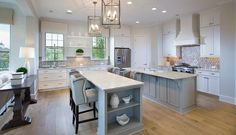 White and gray kitchen features white cabinets paired with white granite countertops and a gray woven tiled backsplash, A white French kitchen hood stands over a stainless steel stove.