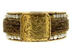 A very unusual Georgian hair ring with the owner's dog depicted on an engraved gold plaque, with a weeping willow and the tomb and a heart behind it. The centre of the shank is woven hair edged with seed pearls. It was made circa 1790 and is in good condition for it's age. It is …