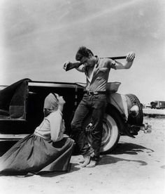 """1955– Elizabeth Taylor and James Dean (that same pose Jimmy is in with arms slung over his rifle would be seen in """"Badlands"""" as Martin Sheen did his best James Dean impersonation throughout the entire film) in a scene from George Stevens' """"Giant."""" –Image© Floyd McCarty"""