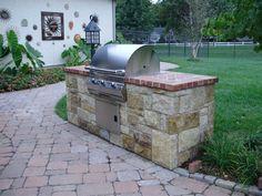 Limestone outdoor kitchen with brick countertop. #TopekaLandscape
