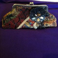 Beautiful vintage appearing clutch Made of a brocade like fabric with detailed appliqué and beading . Brass frame with closure . Small beaded strap on interior so can be carried on wrist. Black satin interior . Excellent condition Bags Clutches & Wristlets