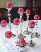 Follow these simple steps to make your Centerpiece of Ornaments on Candlesticks:   Collect candle holders, tall vases, footed bowls, or tall creamers in a mix of heights.   Set an ornament on top of each holder.   Arrange the candle holders around the center of your table.   Special tips for fine-tuning: Use a mix of silver and crystal candlesticks, vases, and containers to form an interesting arrangement.   Choose a mix of shiny and matte ornaments in a range of sizes for special interest…