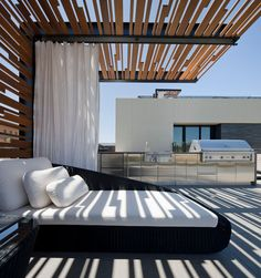 contemporary patio. A custom pool ramada casts dappled shade on a chaise. An identical ramada is partially visible on the roof deck