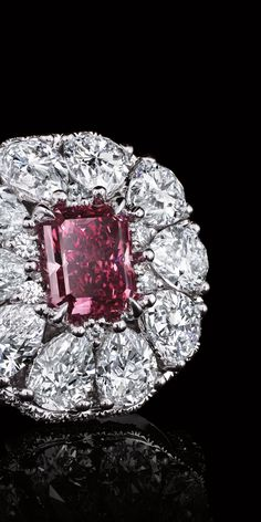 Pear shaped and round brilliant white diamonds bloom around a .59-carat, cut cornered rectangular mixed-cut Fancy Vivid Purplish Pink diamond in this spectacular floral creation.