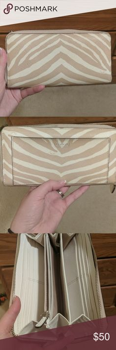 Coach wallet Nuetral (tan and white) zebra striped coach wallet. Large enough to fit phone inside (fits my pixel 2XL with case). Small signs of wear (black dots as shown) Coach Bags Wallets