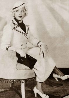 1930s-Fashion-Hollywood-Tries-White-Magic-for-Summer-1934- THERE'S a childish lilt to Mary Carlisle's white gob hat with its navy blue streamers, but her reefer coat is nautical sophistication to its last nickel button!