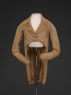 """Homespun"" Coat, About 1805 Though made in a coarse fabric, without interlinings or other professional techniques, the high waist, double-breasted front, dramatic ""M-notch"" lapel, deep cuffs, and turndown collar would all appeal the fashion-conscious man. This cotton and wool blend is an example of ""homespun"" fabric: the fiber was raised, processed, and woven in the US in the effort to establish an American textile industry. Wearing coarse homespun fabric was a patriotic badge of honor."