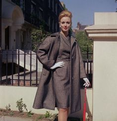 Model wears a grey-brown loose fitting coat worn over a belted matching dress with cross-over neck (1962). #vintage #1960s #fashion