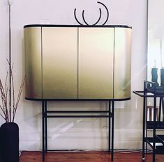 Black sprayed drinks cabinet with brass-clad rounded sides and front on steel legs. #furniture #design #interiordesign #minimalism #lessismore