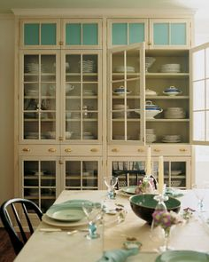 Two floor-to-ceiling built-in storage cabinets with glass fronts enclosed the dining area like a pantry.