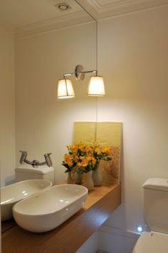 Deborah Roig fez o projeto deste lavabo com bancada de madeir. O espelho toma uma parede inteira, onde está presa uma arandela. A cuba, as louças e os metais são da Deca