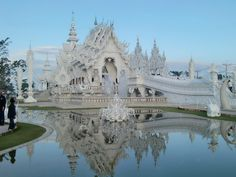 Wat Rong Khun, Chang Rai, Thailand. Visitors must cross a bridge to the temple over a field of fangs and hundreds of pleading white arms and suffering faces of statues reaching up from hell. While stark whiteness predominates, the inside and other parts of the temple compound (including the toilets) are sparkling gold.