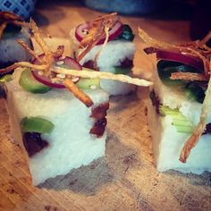 Vegan sushi: pandanrice cooked in coconut milk, smoked and spicy tempeh, spring onion, on top pickled cucumber and red onion, all the way on top ginger floss (fine strips of ginger fried en salted)