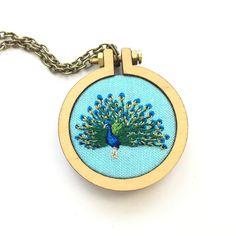 Peacock custom pendant. Making a bird a day a little while ago was a great time and opened up so many ideas. We will never get tired of embroidering our feathered friends. 🐦🐔🐤🐧 . . . #embroidery  #craftposure  #etsy  #thimblethistle #needlework #bordado #contemporaryembroidery #hoopart #modernmaker #broderie #feelingstitchyig #makersmovement #handmadeparade #stitchersofinstagram  #handmadeisbetter  #favehandmade #makeracademy #happysojo #dandelyne #peacock