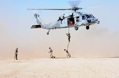 Sailors assigned to Explosive Ordnance Disposal Mobile Unit (EODMU) 8, Detachment Rota, fast-rope down a SH-60S Sea Hawk helicopter during a fast-roping exercise.